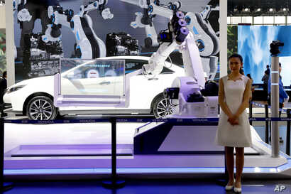 "FILE - An industrial robot is displayed with car during the China Auto 2018 show in Beijing, China, April 26, 2018. Under President Xi Jinping, a program known as ""Made in China 2025"" aims to make the country a tech superpower."