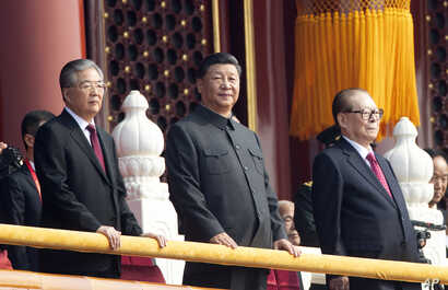 Chinese President Xi Jinping, center, with former presidents Jiang Zemin, right, and Hu Jintao, left, attend the celebration to commemorate the 70th anniversary of the founding of Communist China, in Beijing, Oct. 1, 2019.