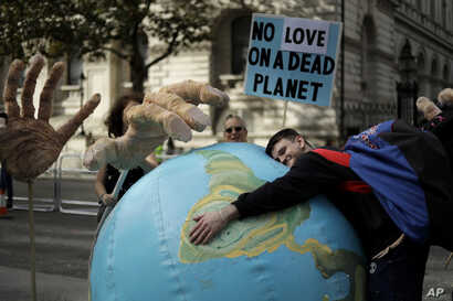 An Extinction Rebellion climate change protester hugs an inflatable planet Earth near Downing Street in London, Britain, Oct. 8, 2019.