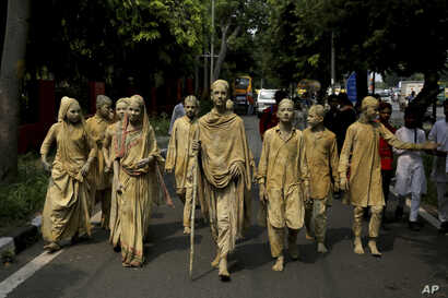 School children dressed as statues depicting Indian freedom leader Mahatma Gandhi's Dandi March cross a road to perform at a traffic intersection on the eve of Gandhi's 150th birth anniversary in New Delhi, India, Oct. 1, 2019.