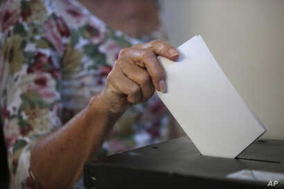 A woman casts her ballot at a polling station in Lisbon, Oct. 6, 2019.