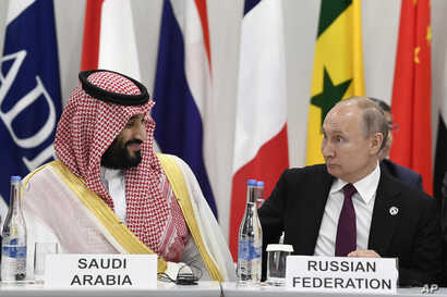 FILE - Saudi Arabia's Crown Prince Mohammed bin Salman, left, talks with Russian President Vladimir Putin during a G-20 summit event in Osaka, Japan, June 28, 2019.