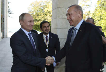 Russian President Vladimir Putin, left, and Turkish President Recep Tayyip Erdogan shake hands before their meeting in the…