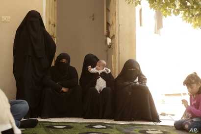 FILE - Women who recently returned from the Al-Hol camp, which holds families of Islamic State members, gather in the courtyard of their home in Raqqa, Syria, during an interview, Sept. 7, 2019.