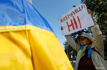 """A woman attends a rally against the approval of a local election accord, in Kyiv, Ukraine, Oct. 2, 2019. Her sign reads: """"No capitulation!"""""""