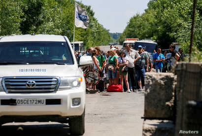 FILE - Cars of the Organization for Security and Cooperation in Europe (OSCE) move as people stand near a checkpoint before crossing the contact line between Russia-backed rebels and Ukrainian troops in Mayorsk, eastern Ukraine, July 3, 2019.