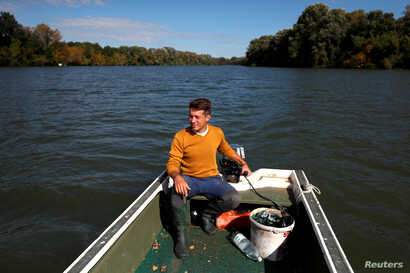 Bence Pardy drives his motorboat on the River Tisza near Tiszafured, Hungary, Oct. 1, 2019.