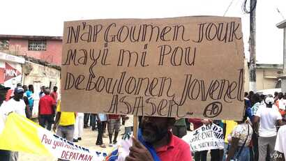 "Protester in Port-de-Paix, Haiti holds sign that reads: ""We'll fight until the corn gets ripe to untangle ourselves from killer Jovenel"", during a protest to demand the president resign, Oct. 4, 2019. (Photo: Lucson Palmeus / VOA Creole)"
