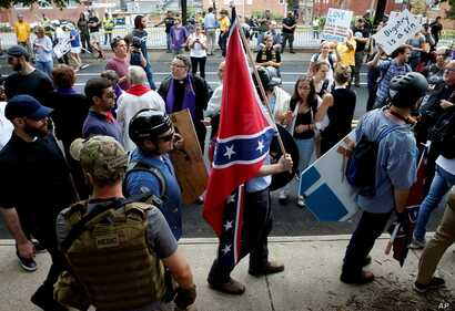 FILE - A white supremacists carries the Confederate flag as he walks past counter demonstrators in Charlottesville, Va., Aug. 12, 2017.