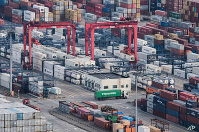 FILE - A cargo truck drives amid stacked shipping containers at the Yangshan port in Shanghai, China, March 29, 2018.
