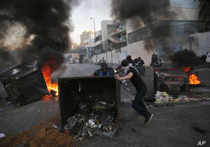 Anti-government protesters block a main highway by a garbage containers and burned tires, during ongoing protests against the Lebanese government, in Beirut, Lebanon, Nov. 4, 2019.
