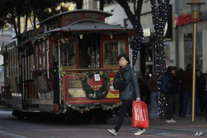 A woman carries a shopping bag while walking in front of a cable car in San Francisco, Friday, Nov. 29, 2019. Black Friday once…