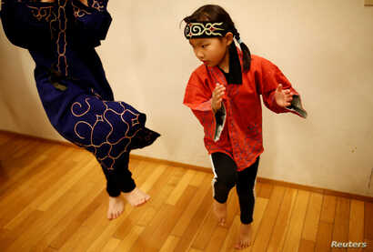 Indigenous Ainu Teruyo Usa's daughter Ruino practices a traditional Ainu dance before performing at a folk art concert in Tokyo…