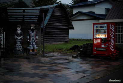 Wooden statues of an Ainu couple stand in front of an Ainu craft shop in the Nibutani district where several Ainu craft shops…