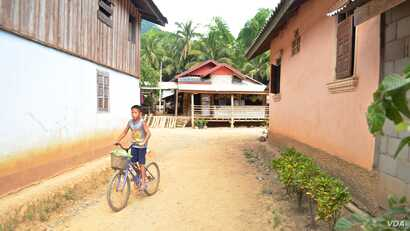 A boy rides his bicycle through Houaygno village, northern Laos, Nov. 4, 2019.