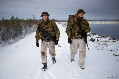Patrol leader Joergen Aas (L) and radio operator Thomas Lundmann patrol the Norwegian side of the Norway-Russia border in Pasvik valley, Finnmark county, Norway, Oct. 23, 2019.