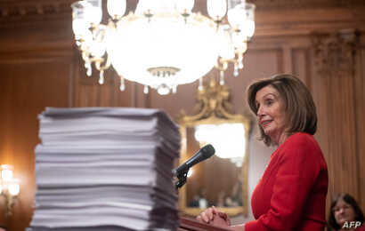 US Speaker of the House Nancy Pelosi speaks alongside a stack of legislation the House has passed as she holds a press…