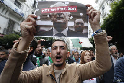 Algerian demonstrators take to the streets in the capital Algiers to reject the presidential elections, in Algiers, Algeria,…
