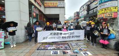 "South Korean college students and activists in Seoul's Hongdae district participate in a demonstration in support of Hong Kong's pro-democracy protests on November 24, 2019. The main banner reads ""Stop the Violent Suppression of Hong Kong Protesters."" VOA/Lee Juhyun"