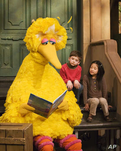 FILE - Big Bird, voiced by Caroll Spinney, reads to children during a taping of Sesame Street in New York, April 10, 2008.