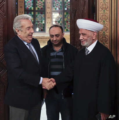 Lebanon's Grand Mufti Sheikh Abdul Latif Derian, right, shakes hand with Samir Khatib, who was once considered a favorite candidate for the post of prime minister, in Beirut, Dec. 8, 2019, in a photo released by the Lebanese government.