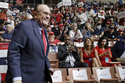 FILE - President Donald Trump's personal attorney Rudy Giuliani smiles as he arrives at Trump's campaign rally in Manchester, New Hampshire, Aug. 15, 2019.