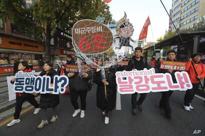 FILE - Protesters march to oppose the United States' demand for raising the defense costs for stationing U.S. troops in South Korea, in Seoul, South Korea, Nov. 16, 2019.