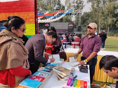 """Author and lawyer Saif Mahmood signs his book """"Beloved Delhi"""" at the queer literature festival. (Anjana Pasricha/VOA)"""