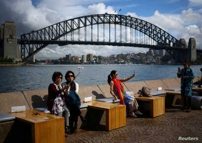FILE - Tourists take photographs with their mobile phones in front of the Sydney Harbor Bridge, in Sydney, Australia, Oct. 13, 2018.