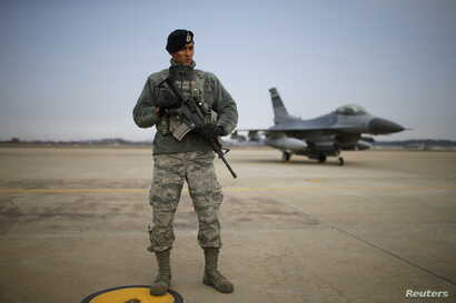 FILE - A U.S. soldier stands guard in front of their Air F-16 fighter jet at Osan Air Base in Pyeongtaek, South Korea, Jan. 10, 2016.