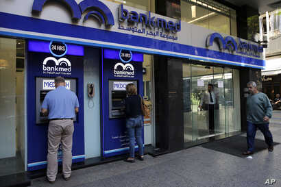 People use an ATM outside a bank, in Beirut, Lebanon, Wednesday, Nov. 20, 2019. Lebanon's worsening financial crisis has thrown…