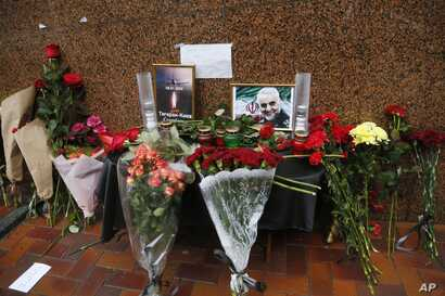 Flowers and tributes are placed outside the Iranian Embassy in Kyiv, Ukraine, Friday, Jan. 10, 2020, with a poster that reads: …