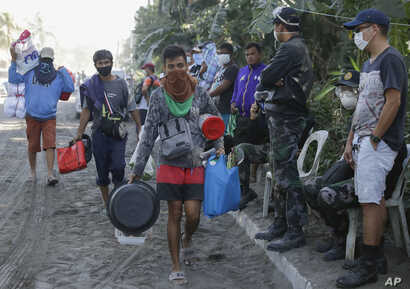 Men carry their belongings as authorities enforced total evacuation of residents living near the active Taal volcano in…