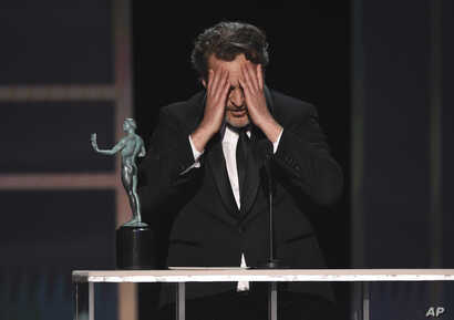 "Joaquin Phoenix reacts as he accepts the award for outstanding performance by a male actor in a leading role for ""Joker"" at the…"