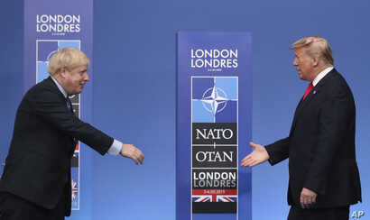 British Prime Minister Boris Johnson, left, reaches out to shake hands with U.S. President Donald Trump at the official arrivals for a NATO leaders meeting at The Grove hotel and resort in Watford, Hertfordshire, England, Dec. 4, 2019.