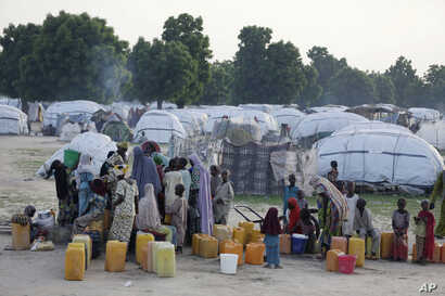 FILE - People displaced by Islamist extremists queue for water at the Muna camp, in Maiduguri, Nigeria, Aug. 30, 2016.