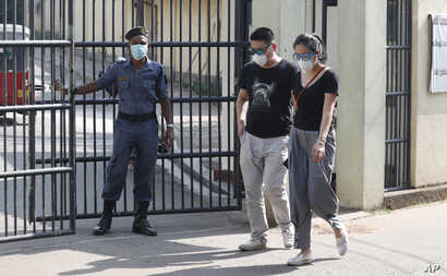 Two Chinese nationals wearing masks leave the infectious diseases hospital in Colombo, Sri Lanka, Jan. 28, 2020.