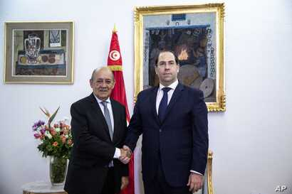 Tunisian Prime minister Youssef Chahed, right, shakes hands with French Foreign Minister Jean-Yves Le Drian, in Tunis, Jan. 9, 2020.