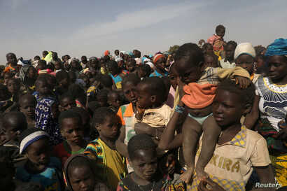 FILE - Displaced children wait for help at a village of Dablo area, Burkina Faso, March 2, 2019.
