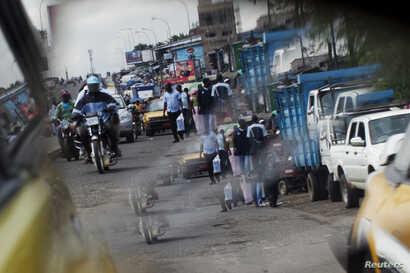 FILE - People ride motorcycles in Douala, Cameroon, Nov. 4, 2013.