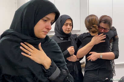 Mourners attend a vigil at University of Toronto student housing for the victims of a Ukrainian passenger jet which crashed in Iran, in a still image from video in Toronto, Ontario, Canada, Jan. 8, 2020.