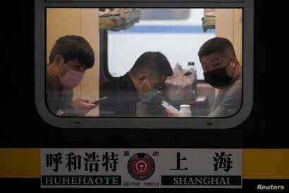 Passengers wearing masks are seen on a train at Shanghai railway station in Shanghai, China, Jan. 21, 2020.