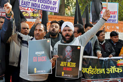 Members of the Confederation of All India Traders (CAIT) hold placards and shout slogans during a protest against the visit of…