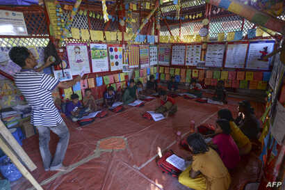 Rohingya children attend a lesson to learn their language at a school at Jamtola refugee camp in Ukhia on December 9, 2019. …