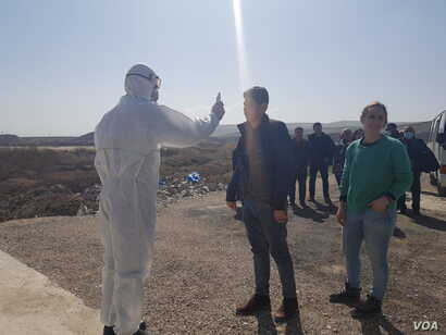 On a land border between Syria and Iraq, health workers take the temperature of travelers as they arrive in Iraq in response to the coronavirus outbreak.  Later that day, the Syria border closed for the same reason, Feb. 27, 2020. (VOA/Heather Murdock)