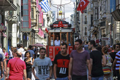 People walk in central Istanbul's Istiklal Avenue, the main shopping road of Istanbul, Wednesday, Aug. 22, 2018. Tourists have…
