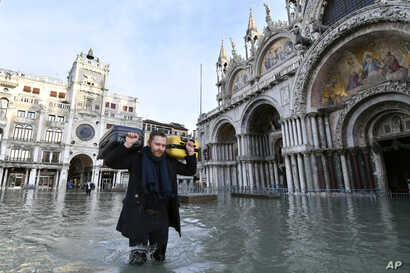 A man carries suitcases as he wades through water during a high tide of 1.44 meters (4.72 feet), in St. Mark's Square, in…