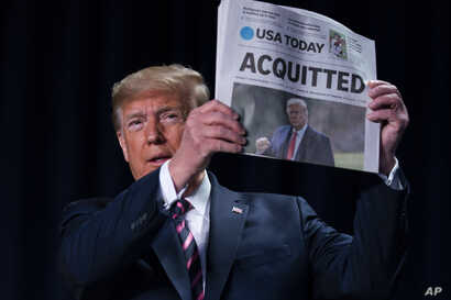 """President Donald Trump holds up a newspaper with the headline that reads """"ACQUITTED"""" at the annual National Prayer Breakfast."""