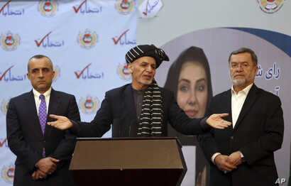 Afghan President Ashraf Ghani, center, speaks at the Afghan Independent Election Commission after receiving the official…