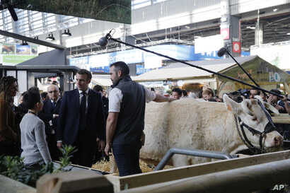 French President Emmanuel Macron speaks with a farmer during a visit to the International Agriculture Fair (Salon de l…